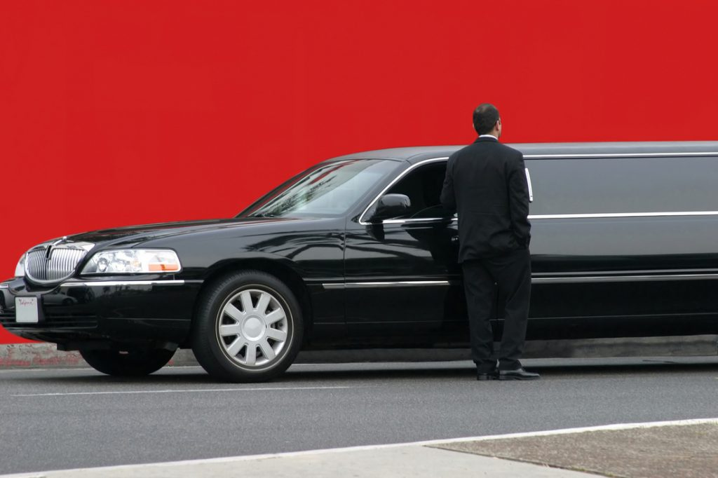 limo and driver in front of red wall near airport