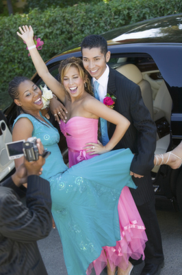 Three friends posing outside of a limousine before homecoming dance