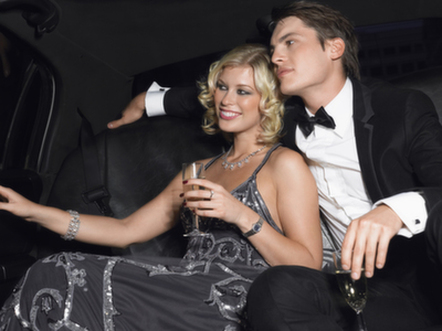 Well-dressed young couple in a limo with champagne