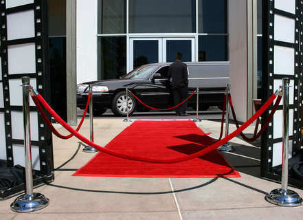 Limousine and driver in front of red carpet