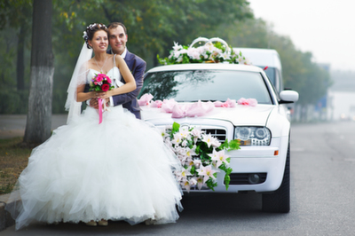 Couple in front of a decorated limousine